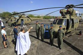 A military chaplain sprinkles Holy Water on brand new Polish Sokol multi-role helicopters during turnover ceremony to the Philippine Air Force at Clark Air Base, Pampanga province (AP).
