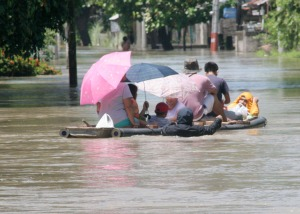 BANCA RIDE. Residents ride on a banca at this flooded road in barangay Lasip in Calasiao, last September 17. Most areas in the town are still underwater several days after the heavy rains caused by southwest monsoon enhanced by typhoon Luis last September 14.CESAR RAMIREZ