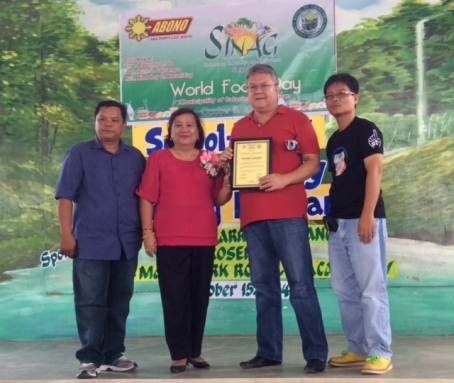 """APPRECIATION. Former 5th District Rep. Mark O. Cojuangco receives plaques of appreciation from school officials of Calasiao Central School (left to right): Principal Roberto Z. Barongan, District Supervisor Dr. Thelma E. Royeca and PTA President Lito G. Senieto during the Sinag's sponsored """"school-based feeding program"""" in celebration of World Food Day last October 15. VIRGIL MAGANES"""