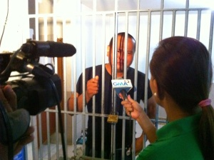BEHIND BARS. Mangaldan Poblacion Barangay Chairman Jojo Quinto, a dentist, tearfully tells media men last December 3 how he and Councilwoman Tonette Morillo were arbitrary arrested by the police and thrown to jail after they violated the 60-day preventive suspension imposed on them by Mayor Bona Fe D. Parayno. (Contributed photo)