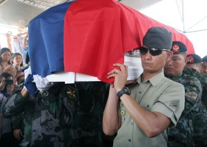 Army Corporal Marcos Mejia(right) joins policemen in carrying the casket bearing the remains of his older brother, PO2 Ephraim Mejia.