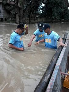 WAIST DEEP. Police men lead by Calasiao's Chief of Police Supt. Rizaldy Dalope   (extreme left) measureS the waist depth of  flood brought by Typhoon Lando that swamped recently some villages in the Central Pangasinan's town